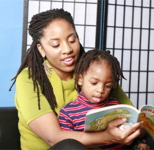 teacher teaching her pupil how to read